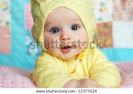 Baby Girl in Yellow Knit Hooded Sweater in Front of Quilt - stock photo