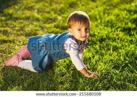 Baby-girl is crawling at the green lawn. Cute little girl is having fun in the sunlit garden crawling and smiling looking in camera. Happy childhood concept. - stock photo