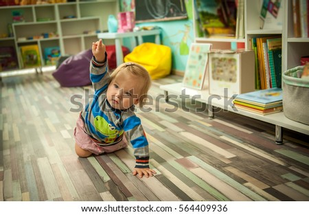 Baby Girl Is Crawling On The Floor. Modern Bright Child Room. Cushioned  Furniture,