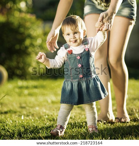 Baby girl is doing her first steps with mothers help. Cute little girl learns to walk with her young mom helping her in the sunny garden outdoors. Happy childhood and motherhood concept. Instagram. - stock photo