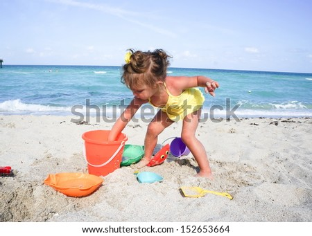 baby girl is having fun at the beach