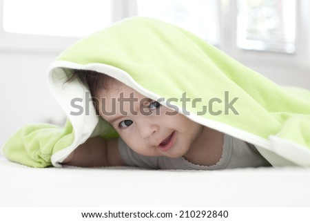 Baby girl is hiding under the white and green blanket - stock photo