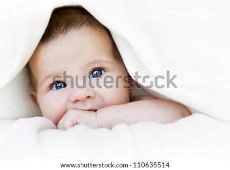 baby girl is hiding under the white blanket - stock photo