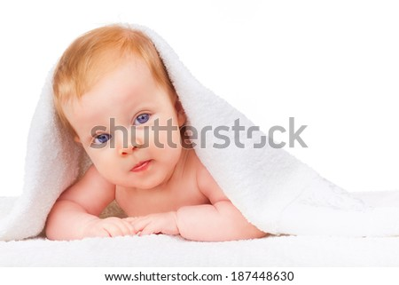 Baby girl is hiding under the white blanket on a white background