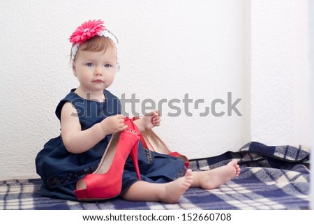 Baby girl is holding adult high heel shoes - stock photo