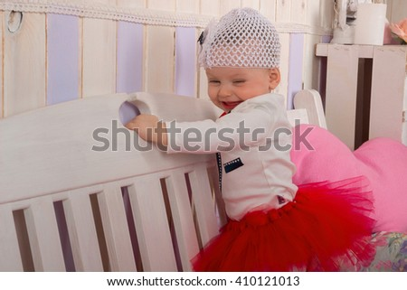 Baby girl is laughing while standing on the bench