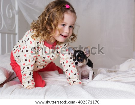 Baby girl is sitting on bed with chihuahua dog - stock photo