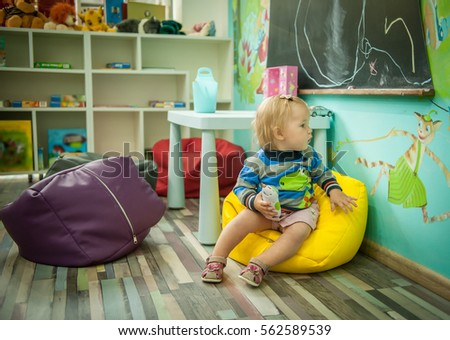 Baby Girl Is Sitting On The Floor. Modern Bright Child Room. Cushioned  Furniture,