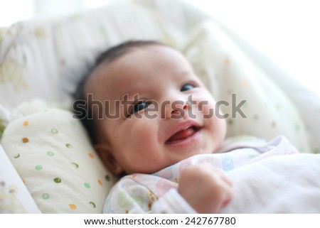 Baby girl is smiling and laugh on her cradle - stock photo