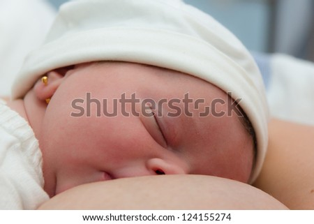 Baby girl just born sleeping after her first time nursing - stock photo