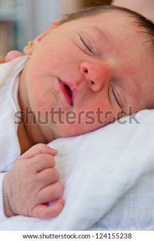 Baby girl just born sleeping on her mother's shoulder - stock photo