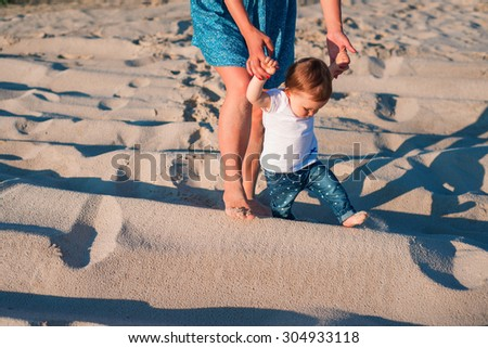 Baby girl learn to walk with her mother on the beach. mother holding child hands - stock photo