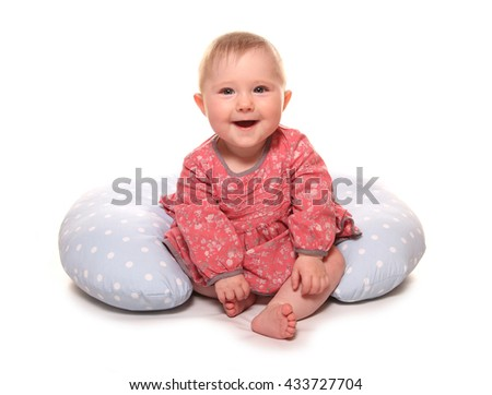 Baby girl learning to sit using a pillow cutout - stock photo