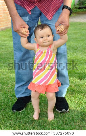 Baby girl learning to walk with the help of an adult  - stock photo