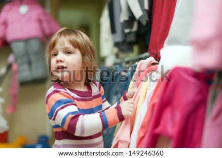 Baby girl looking at clothes in fashionable shop - stock photo