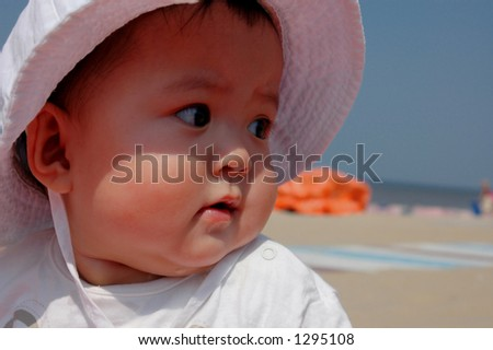 baby girl looking at the beach - stock photo