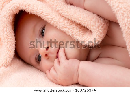 Baby girl looks as if she is biting her nails - stock photo