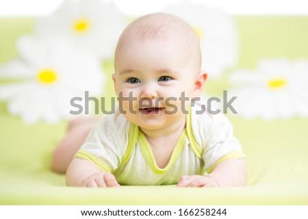 baby girl lying on green meadow among daisy - stock photo