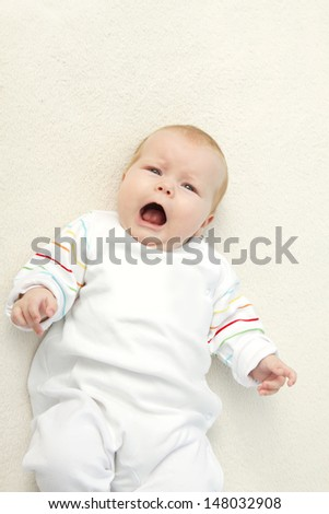 baby girl lying on the bed - stock photo