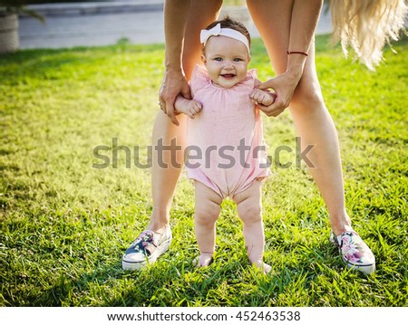 Baby girl making first steps with mother holding her  - stock photo