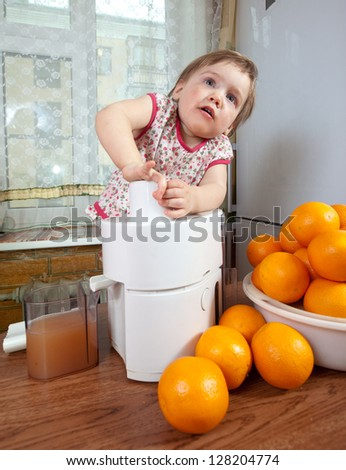 Baby girl making fresh orange juice in home kitchen - stock photo