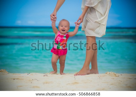 baby girl making her first steps holding mother's hands on the sea shore