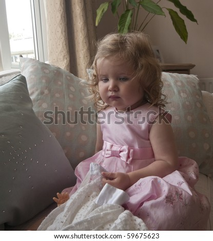 Baby girl,  nearly two years old, on a sofa with cushions at home, in a pink dress posing for the camera with her security blanket.