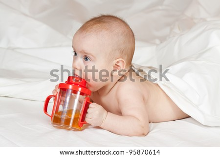 Baby girl of 5 months with sippy cup on white blanket - stock photo
