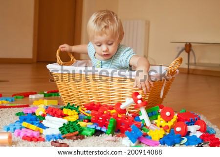 Baby girl of one year old in basket with toys - stock photo