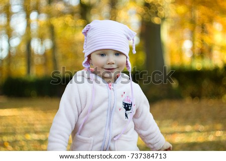 Baby girl on autumn park for thematic background.