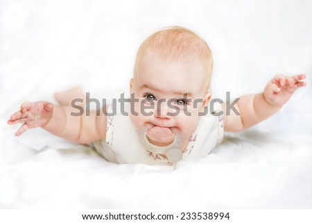 Baby girl on her stomach with hands spread apart and teethers in the mouth - stock photo