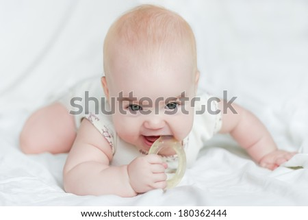 Baby girl on her stomach with teether in the mouth - stock photo