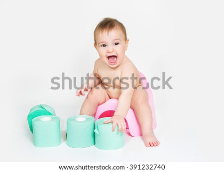 Baby girl on potty and toilet paper - stock photo