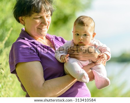 Baby girl on the hands of her grandmother in nature