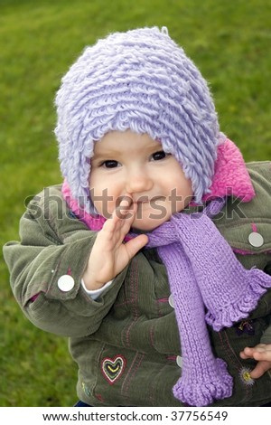 Baby girl outdoors sitting on the grass