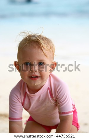 baby girl playing at the beach