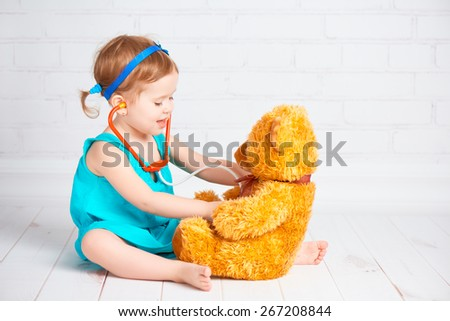 baby girl playing doctor and treats teddy bear - stock photo