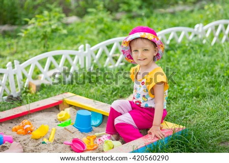 Baby girl playing in a sandbox in the garden