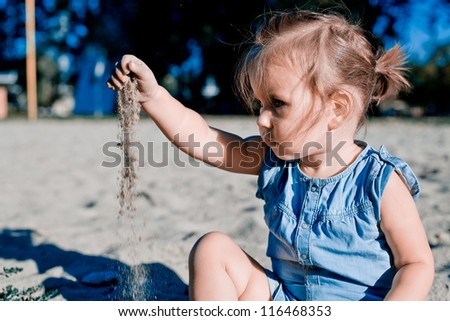 Baby girl playing in sand