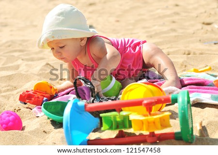baby girl playing on the beach - stock photo