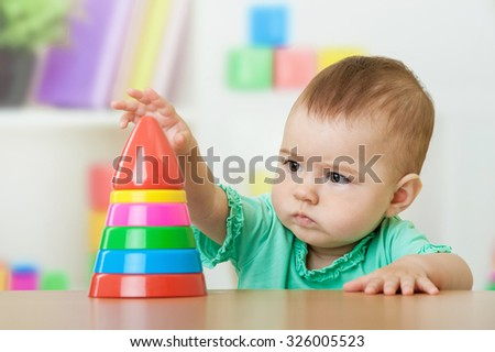 Baby girl playing with a pyramid toy