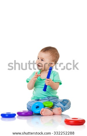 Baby girl playing with a pyramid toy, isolated on white