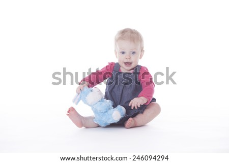 baby girl playing with blue bunny toy on white background - stock photo
