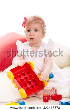 Baby girl playing with colorful construction cubes home - stock photo