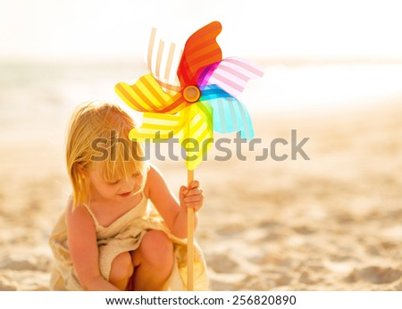Baby girl playing with colorful windmill toy on beach - stock photo