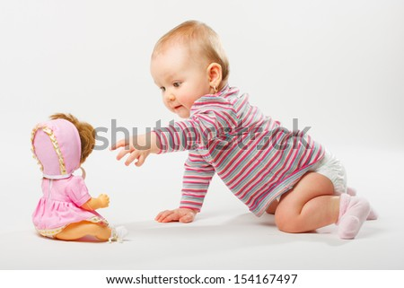 Baby girl playing with doll