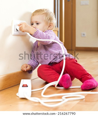 Baby girl playing with electrical extension and outlet  at home - stock photo