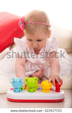 Baby girl playing with musical toy animals home