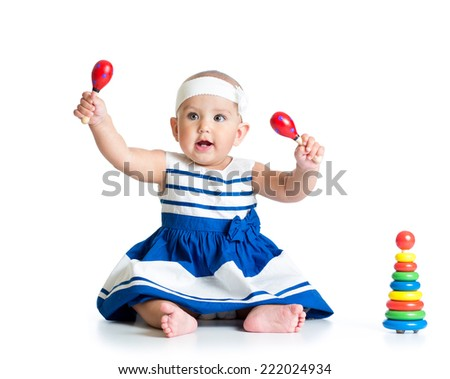 Baby girl playing with musical toys. Isolated on white background
