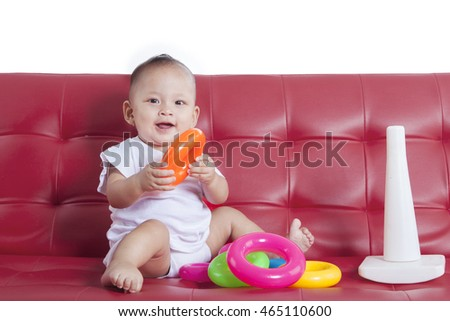 Baby girl playing with pyramid toy while sitting on the couch, isolated on white background